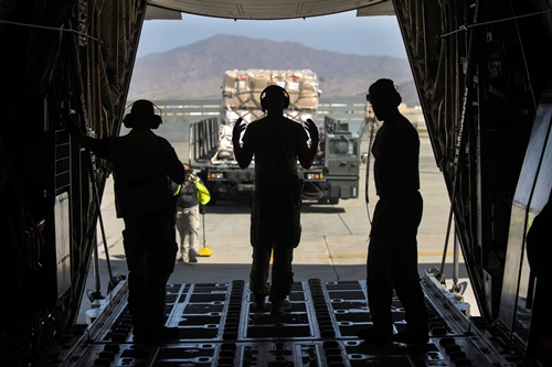 """Hand Signals"" Air Force Senior Airman Andrew Garrett, center, uses hand signals to direct a vehicle off a C-130J Super Hercules aircraft at Bagram Airfield, Afghanistan, Aug. 19, 2016. Garrett is assigned to the 774th Expeditionary Airlift Squadron. Air Force photo by Senior Airman Justyn M. Freeman"
