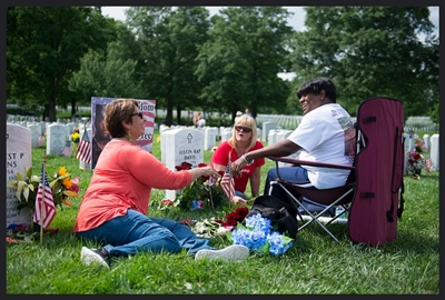 Elva Hernandez, Suzy Maddox, and Paula Davis sit in front of Davis' son's gravesite in Sect. 60 of Arlington National Cemetery, Arlington, Va., May 29, 2017. All three women have sons buried in Sect. 60 - Corp. Joseph Michael Hernandez, U.S. Army; Sgt. Matthew William Maddox, U.S. Army; and PFC Justin Ray Davis, U.S. Army. They come to the cemetery every Memorial Day to remember those they have lost. (U.S. Army photo by Elizabeth Fraser / Arlington National Cemetery / released)